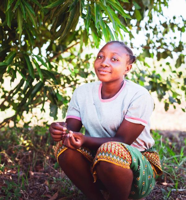 Junge Frau sitzt in der Natur